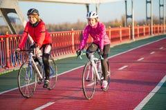 2 молодых женских велосипедиста ехать велосипеды дороги на линии велосипеда моста в холодном солнечном дне осени уклад жизни прин Стоковая Фотография