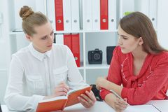 2 молодых женских делового партнера обсуждая идеи на встрече в офисе Стоковая Фотография