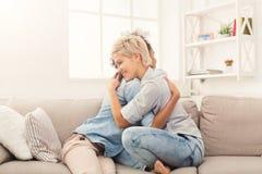 2 молодых женских друз обнимая дома Стоковые Изображения