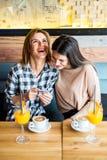 2 молодых женских друз сидя в кафе, выпивая кофе и ju Стоковое Изображение RF