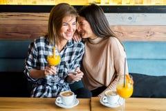 2 молодых женских друз сидя в кафе, выпивая кофе и ju Стоковое Фото