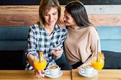 2 молодых женских друз сидя в кафе, выпивая кофе и ju Стоковые Изображения RF