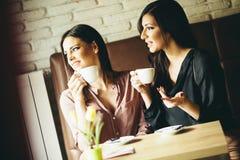 2 молодых женских друз сидя в кафе и кофе питья Стоковая Фотография RF