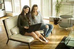 2 молодых женских друз сидя в комнате на софе и использовании Стоковые Фотографии RF