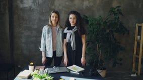 2 молодых женских коллеги дела стоят совместно в офисе стиля просторной квартиры, представляют и смотрят камеру Девушки видеоматериал