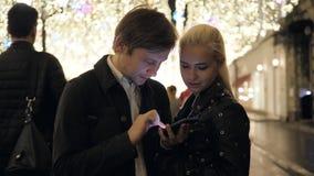 2 молодых женских мужских друз беседуя и смотря их smartphone на ноче улицы, человеке и студенте женщины счастливом акции видеоматериалы