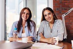 2 молодых женских предпринимателя сидя на столе работы во время деловой встречи в современном конференц-зале Стоковое Фото