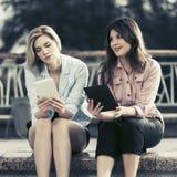 2 молодых женщины моды используя цифровые планшеты внешние стоковое фото