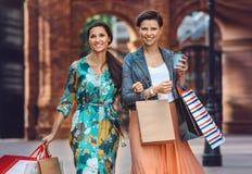 2 молодых женщины моды с хозяйственными сумками в городе Стоковые Фотографии RF