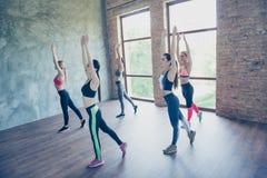 5 молодых женщин спорта размышляют пока практикующ йогу внутри Стоковое Фото