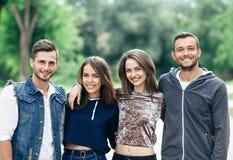 4 молодых жизнерадостных друз идя на теплый день Стоковые Изображения RF