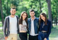 4 молодых жизнерадостных друз идя на теплый день Стоковая Фотография RF