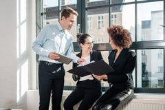 3 молодых жизнерадостных работника усмехаясь в современном офисе Стоковые Изображения RF