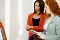 2 молодых кавказских женщины стоя в фронте художественной галереи картин Стоковая Фотография