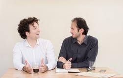 2 молодых кавказских коллеги обсуждая на таблице в офисе с светлой предпосылкой Стоковые Фото