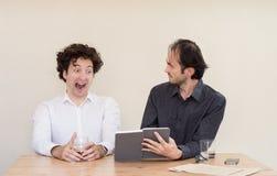 2 молодых кавказских коллеги обсуждая на таблице в офисе с светлой предпосылкой Стоковая Фотография