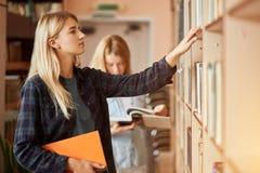2 молодых книги shooses студенток на библиотеке стоковое изображение