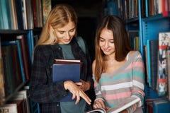 2 молодых книги shooses студенток на библиотеке стоковые изображения