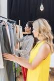 2 молодых красивых женщины выбирая одежды Стоковые Фото