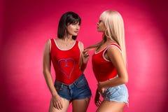 2 молодых красивых женщины представляя в студии в шортах, фитнесе стоковое фото rf