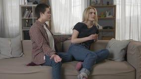 2 молодых лесбосских девушки сидят на кресле, враждующ, споря, конфликт, девушка с короткими волосами извиняются к сток-видео