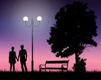 2 молодых любовника держа руки под деревом и накаляя лампой с Стоковое Изображение