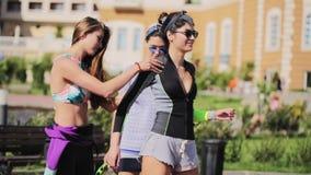 3 молодых милых девушки делают тренировки фитнеса снаружи на солнечный день сток-видео