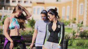 3 молодых милых женщины делают тренировки фитнеса снаружи на солнечный день сток-видео
