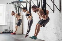 3 молодых мужских и женских взрослого делая тягу поднимают на кольцах стоковая фотография rf