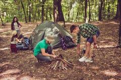 2 молодых мужских туриста в древесине, организуя огонь fo лагеря Стоковая Фотография RF