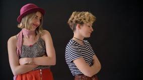 2 молодых очаровывая женских друз имеют конфликт, обиденные женщин стоя при пересеченные руки изолированные на черной предпосылке сток-видео