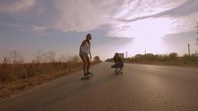 2 молодых подходящих женщины курсируя на longboards во время летних каникулов видеоматериал