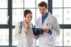 2 молодых преданных доктора анализируя совместно рентгенограмму ноги Стоковые Изображения RF