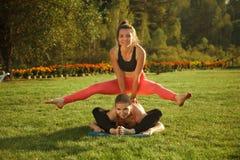 2 молодых привлекательных девушки практикуя йогу внешнюю Стоковое Фото
