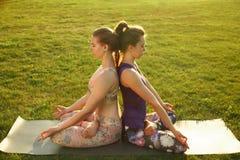 2 молодых привлекательных девушки практикуя йогу внешнюю Стоковые Фотографии RF