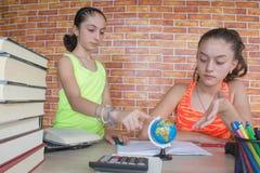2 молодых привлекательных девушки студента изучая уроки Стоковые Фото