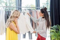 2 молодых привлекательных женщины выбирая одежды Стоковое Изображение RF