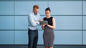 2 молодых профессиональных бизнесмены приветствию тряся руки работая как команда используя планшет видеоматериал