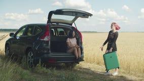 2 молодых разнообразных женщины с чемоданами на отключении автомобиля видеоматериал