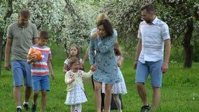2 молодых семьи с уставшими детьми после дня в природе Зацветать фруктовых деревьев акции видеоматериалы