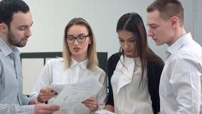 4 молодых сотрудника офиса идя через представление дела Стоковые Фотографии RF