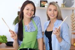 2 молодых счастливых женщины варят в кухне Друзья имеют потеху пока preapering здоровая и вкусная еда Стоковые Изображения RF