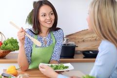 2 молодых счастливых женщины варят в кухне Друзья имеют потеху пока preapering здоровая и вкусная еда Стоковые Изображения