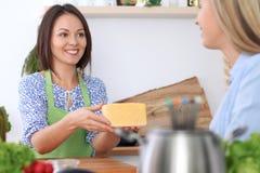 2 молодых счастливых женщины варят в кухне Друзья имеют потеху пока preapering здоровая и вкусная еда Стоковые Фото