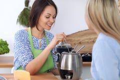 2 молодых счастливых женщины варят в кухне Друзья имеют потеху пока preapering здоровая и вкусная еда Стоковое Изображение RF