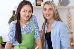 2 молодых счастливых женщины варят в кухне Друзья имеют потеху пока preapering здоровая и вкусная еда Стоковое Изображение