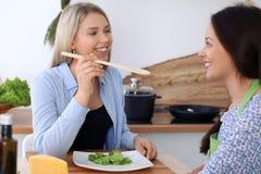 2 молодых счастливых женщины варят в кухне Друзья имеют потеху пока preapering здоровая и вкусная еда Стоковые Фотографии RF