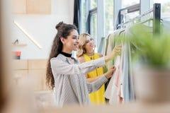 2 молодых счастливых женщины выбирая одежды Стоковое Изображение