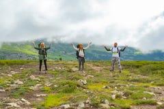 3 молодых туриста при backpackers стоя в ряд на hil стоковые изображения