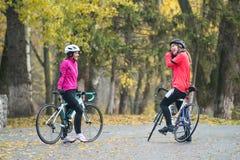 2 молодых усмехаясь женских велосипедиста при велосипеды дороги отдыхая и в парке в холодном дне осени Здоровый уклад жизни Стоковые Фото